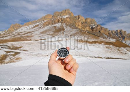 A Man S Hand Holds A Pocket Magnetic Compass For Navigation Against The Backdrop Of Winter Rocky Slo