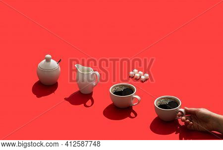 White Cup With Fresh Black Coffee And Sugar Cubes, Cream Jug, Sugar Bowl And Womans Hand Holding Cof