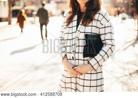 Woman In Coat With Clutch Bag Posing On The City Streets