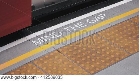 Mind The Gap Sign. Text On Train Station Platform. White Text Signal On Metro Or Underground Floor.