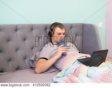 A Young Man In Headphones Lies Reclining In A Bed Under A Multicolored Plaid And Watches Video Or Wo