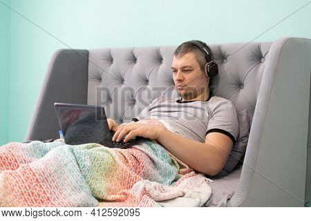 A Young Man Freelancer In Headphones Lies Reclining In A Bed Under A Multicolored Plaid And Watches