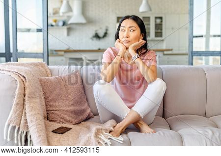 Slender Chinese Woman Sitting Cross-legged On The Grey Sofa With Plaid In The Living Room, Looking A