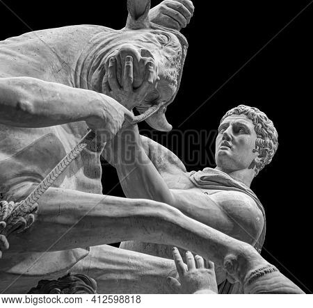 Hercules fighting the Cretan Bull or statue of the god Mithras killing a bull. Stone sculpture isolated on black background