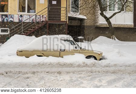 Lutsk, Ukraine - February 12,2020: City Street After Blizzard. Stuck Car In Snow And Ice. Buried Veh
