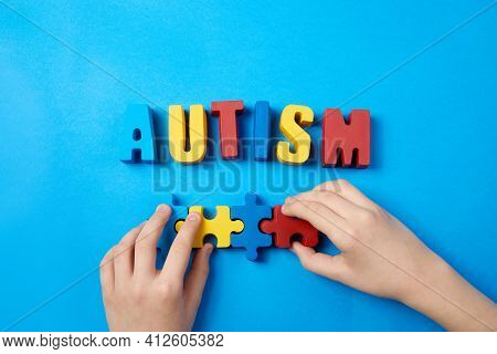 Autistic Kid Hands Holding Puzzle Jigsaw And Word Autism, Mental Health Concept. Autism Spectrum, Di