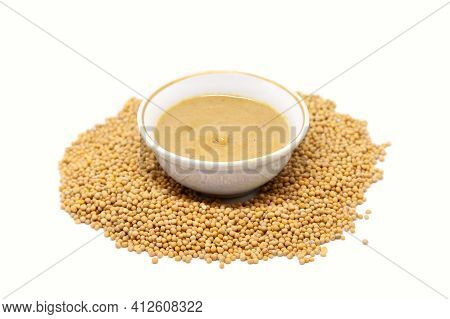 Mustard Sauce In A Bowl With Mustard Seeds. Isolated On White Background