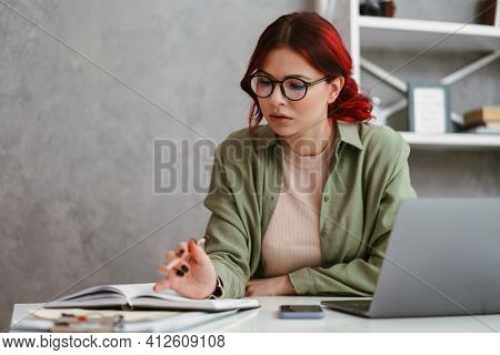 Young focused woman with red hair writing down notes while working with laptop in office
