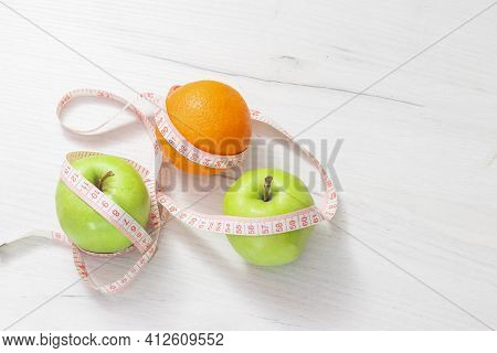 Measuring Tape Wrapped Around Two Green Apple And Orange Isolated On White Background, Concept Of Th