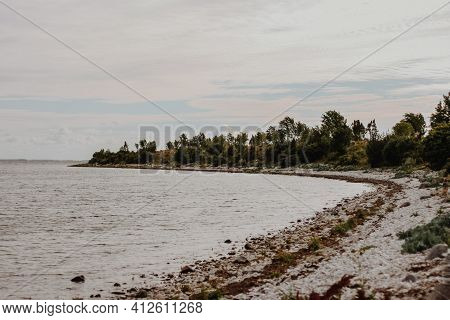 Rocky Beach Landscape With Sea Water And Green Trees On The Shore. The Shore Is Winding. Summer Land
