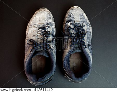 Pair Of Worn Out Dirty Mens Sneakers On Black Background.