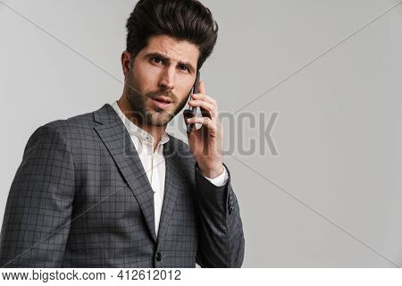 Perplexed young man in jacket posing and talking on mobile phone isolated over grey background