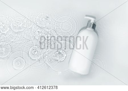 White Body Lotion Bottle On White Water Background With Drops, Top View, Copy Space. Moisturizing Sk