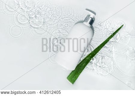 White Body Lotion Bottle And Aloe Vera Leaf On White Water Background With Drops, Top View, Copy Spa