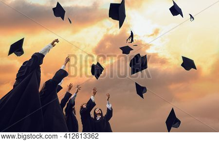 Graduates In Black Robes Throwing Up Their Academic Hats Against The Backdrop Of A Magical Sunset.