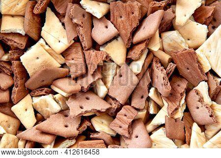 Top View Of Chocolate Graham Crackers Broken Into Pieces Of Crumbs. Background Graham Crackers