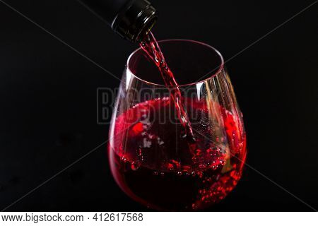 Pouring Red Wine With Splashes And Drops Into A Glass On A Black Background.