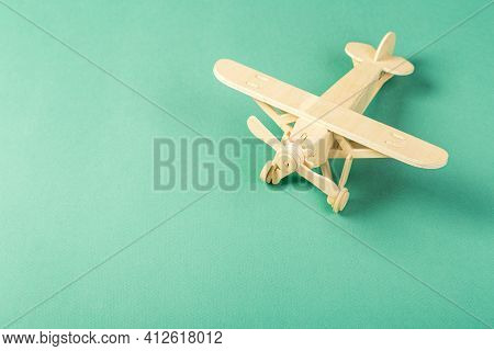 Model Of A Wooden Toy Plane, Airliner, On A Green Background. The Concept Of Travel And Transport An