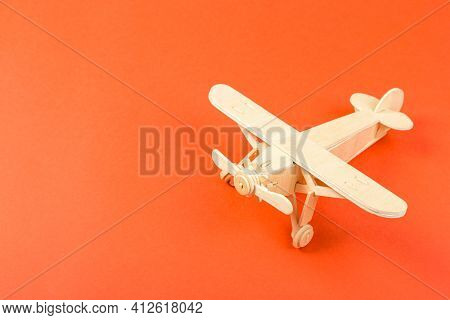 Wooden Model Of A Passenger Plane With On An Orange Background. Tourism And Travel Concept.
