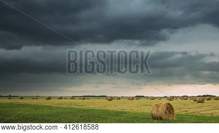 Dramatic Sky Before Rain With Rain Clouds On Horizon Above Rural Landscape Field Meadow With Hay Bal
