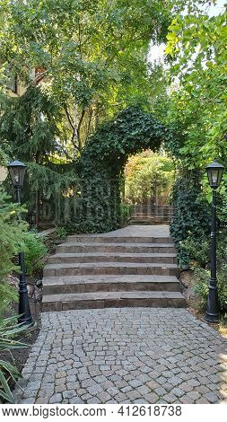 Path Through Arched Gateway To English Garden With Retro Streetlights By Sides. Stone Paved Stairs I