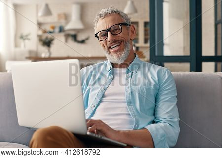 Senior Man In Casual Clothing Using Laptop And Looking At Camera With Smile While Sitting On The Sof