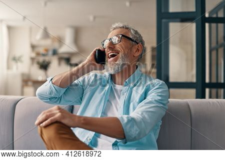 Smiling Senior Man In Casual Clothing And Eyeglasses Talking On The Smart Phone While Sitting On The
