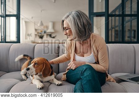 Cheerful Senior Woman In Casual Clothing Spending Time With Her Dog While Sitting On The Sofa At Hom