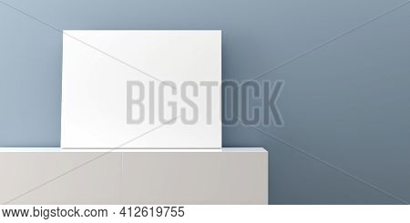 White Empty Poster Or Picture Mock-up Template On White Sideboard In Front Of Blue Wall Background,