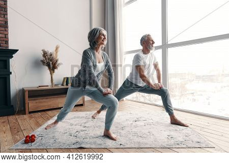Beautiful Senior Couple In Sports Clothing Exercising And Smiling While Spending Time At Home