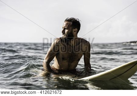 Hipster Surfer Sitting On His Surfboard Into The Ocean Water And Waiting For A Big Wave - Fit Bearde
