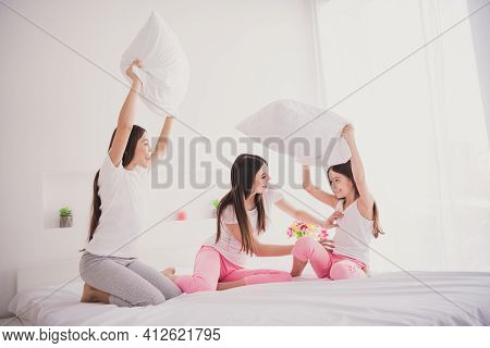Photo Of Charming Pretty Three Siblings Nightwear Sitting Bed Smiling Fighting Pillows Indoors Insid