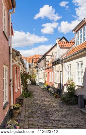 Colorful slanted houses on cobbled medieval street at the old town of Aalborg, Denmark