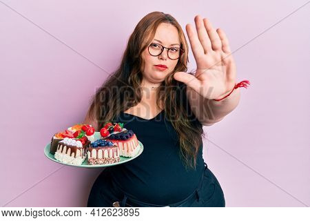 Plus size caucasian young woman holding cake slices with open hand doing stop sign with serious and confident expression, defense gesture