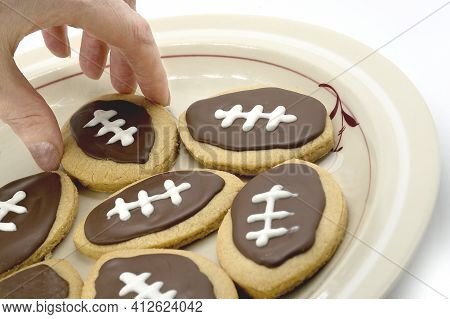Football Shape Cookies On Plate. Hand Taking Cookie From Plate. Home Made Cookies Concept. American