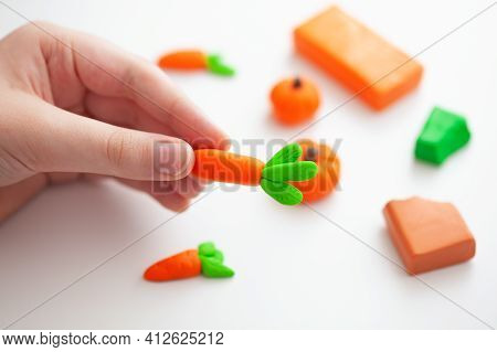 A Young Boy Making Polymer Clay Vegetables. Shallow Depth Of Field. Close Up.