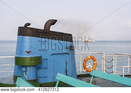 Smoke From Ferry Boat Flue During Sea With Sunlight, Sea Water And Blue Sky In Background, Thailand.