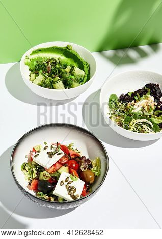 Greek salad, cheese and beet salad and cucumbers with chuka seaweed. Salad bowl on white table with green wall. Sunlight with harsh shadow of green tropic leaf