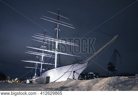 Vintage White Sailing Ship Is Moored In Turku At Night In Snowy Winter, Finland