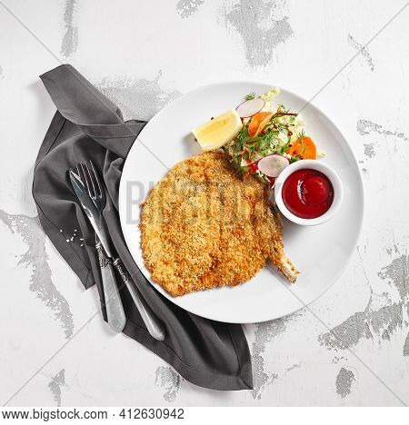 Schnitzel chicken plate with salad, lemon and sauce. Chicken or pork meat german fast food on white table