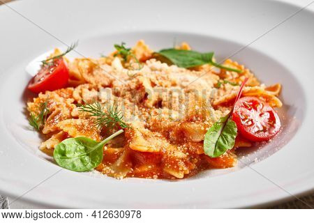 Farfalle pasta food on white table. Pasta restaurant plate with basil leaf and tomato, red tomato sauce. Delicious italian pasta