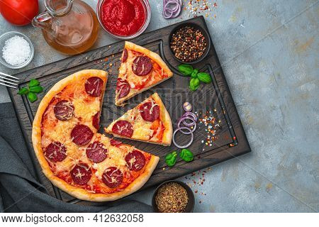 Pepperoni Pizza And Ingredients On A Cutting Board On A Gray Background. The Concept Of Culinary Bac