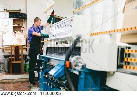 Glazier worker operates glass cutting machine in workshop. Industry