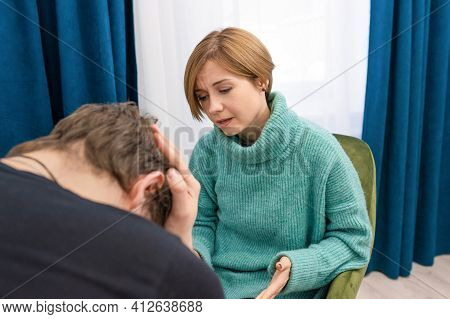 Young Man During Therapy In A Psychologists Office. A Female Psychologist Advises A Man During A Psy