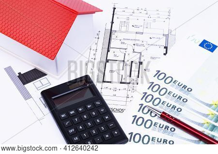 The Photo Shows A Model House On An Expose With Calculator, Money And Ballpoint Pen