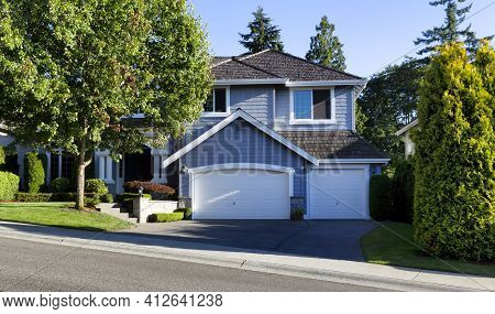 Curb View Of A Modern Home With Cedar Shake Roof During Summer Morning