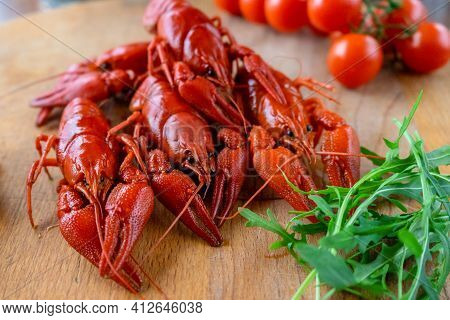 Boiled Red Crayfish Lie On A Wooden Table, Fresh Herbs And Tomatoes.concept:beer Appetizer, Delicacy