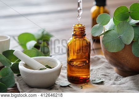 Bottle Of Eucalyptus Oil, Mortar And Wooden Bowl Of Green Eucalyptus Leaves. Close Up Of A Drop Of E