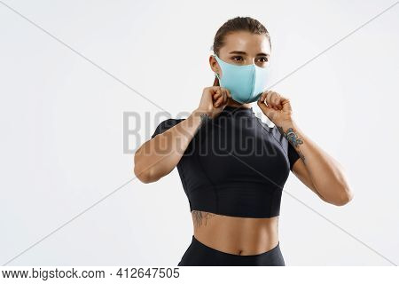 Portrait Of Fit Woman Putting On A Protective Face Mask And Workout. Sporty Female Athlete Wearing F
