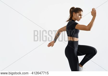 Determined Muscular Female Athlete Workout, Raising Leg And Doing Stretching Exercises. Sport Woman